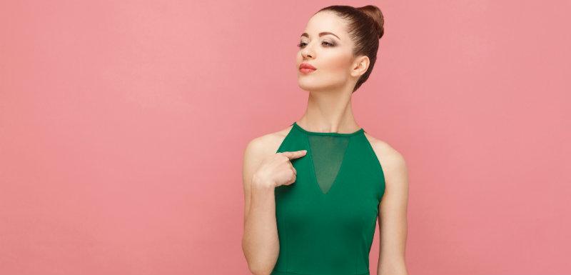 Fille fière en robe verte devant un mur rose saumon