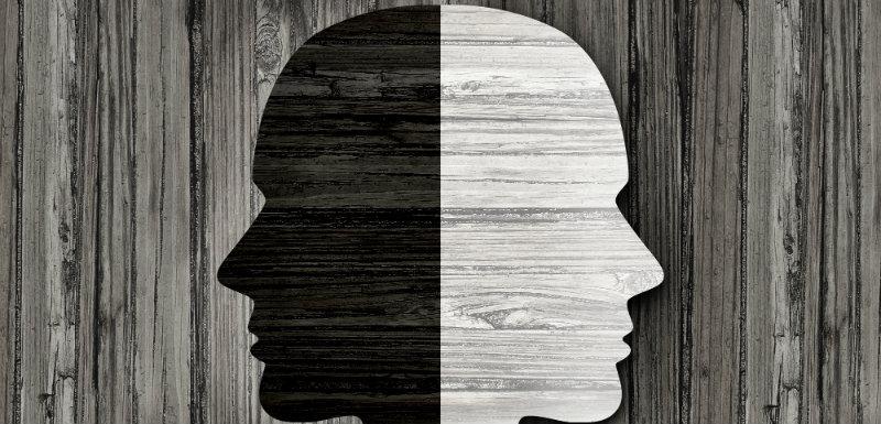 Double visage blanc et noir sur un fond en bois où on tente de le diagnostic